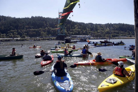 Kayakers gather as activists hang from the St. Johns Bridge in an effort to stop the Royal Dutch Shell PLC icebreaker Fennica from departing in Portland, Ore., Thursday, July 30, 2015. The Fennica left dry dock and made its way down the Willamette River toward the Pacific Ocean soon after authorities forced the demonstrators from the river and the St. Johns Bridge. (AP Photo/Don Ryan)